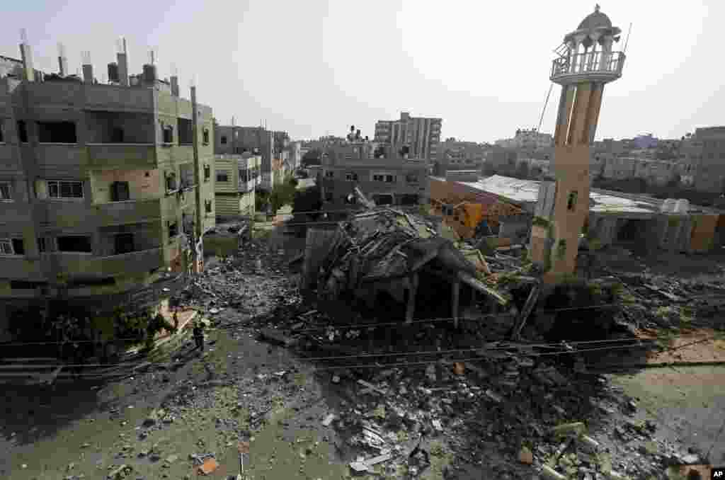 Palestinians walk around the ruins of the Al-Tawfeeq Mosque after it was hit by an overnight Israeli missile strike in the Nuseirat refugee camp, central Gaza Strip, July 12, 2014.