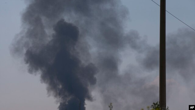 Black smoke rises from a shot down Ukrainian Army helicopter outside Slovyansk, Ukraine, May 29, 2014.