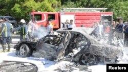 Petugas pemadam kebakaran Suriah memadamkan mobil yang terbakar pasca serangan bom di distrik Mazzeh, Damaskus, Senin (29/4). PM Suriah lolos dari serangan bom mobil ini.