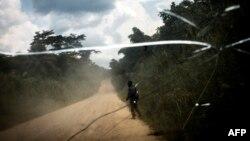 Un homme marche sur la route de transport qui relie la ville de Bunia à la ville minière de Mambasa, dans la province de l'Ituri, le 10 juillet 2018.