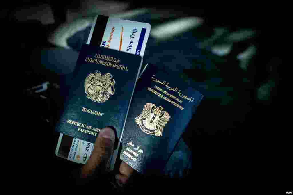 A Syrian-Armenian national holds his Syrian and Armenian passports at the Zvartnots Airport, December 2012. (VOA/D. Markosian)