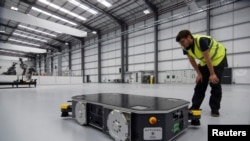 """An engineer at UK electric van and bus maker Arrival inspects a specially developed autonomous robot at the startup's low-cost """"microfactory"""" in Bicester, Britain, August 3, 2021. Picture taken August 3, 2021. REUTERS/Nick Carey"""