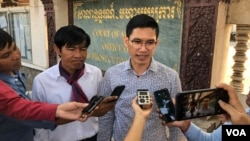 FILE: Uon Chhin and Yeang Sothearin, former RFA reporters talk to reporters outside of appeal court on 23 December, 2019. (Tum Malis/VOA)