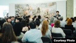 미국 워싱턴의 카젠미술관에서 큐레이터 문범강 교수가 북한화가 6명의 공동작품 '댐의 완공을 기쁨으로 기대하며'(2015년 작)를 관람객들에게 설명하고 있다. 사진 제공 = 노체인.