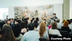 미국 워싱턴의 카젠미술관에서 큐레이터 문범강 교수가 북한화가 6명의 공동작품 '댐의 완공을 기쁨으로 기대하며'를 관광객들에게 설명하고 있다. 사진 제공 = 노체인.