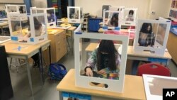 In this March 2, 2021, file photo, socially distanced and with protective partitions students work on an art project during class at the Sinaloa Middle School in Novato, Calif. (AP Photo/Haven Daley, File)