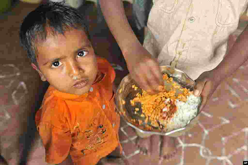 An Indian boy mixes rice and pickle to feed his brother at his home in a slum in Hyderabad, January 10, 2012. (AFP)