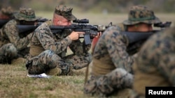 FILE - U.S. Marines take part in marksmanship qualification at Guantanamo Bay U.S. Naval Base, March 6, 2013.