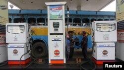 Một nhân viên đang đổ xăng cho một chiếc xe buýt tại một cây xăng ở thành phố Kolkata, Ấn Độ