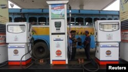 An employee fills diesel in a public bus at a fuel station in Kolkata, August 13, 2012.