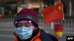 一名戴着口罩和眼罩的男子行走在北京街头。(2020年2月12日)