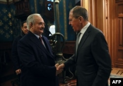 FILE - This handout picture released by the Russian Foreign Ministry Jan. 13, 2020, shows Russian Foreign Minister Sergey Lavrov welcoming Libyan military strongman Khalifa Haftar in Moscow.
