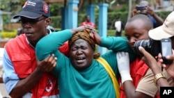 Wafanyakazi wa Msalaba Mwekundu wakimsaidia mama kutafuta mwili wa mwanawe