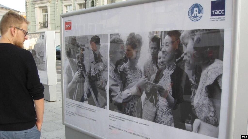 俄羅斯官媒塔斯社去年夏季在莫斯科舉辦介紹中俄友誼圖片展覽。 一位行人在觀看50年代有關中蘇友誼的圖片。 (美國之音白樺拍攝)