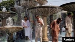 Men cool off from the heatwave, as they shower at a water fountain along a road in Karachi, Pakistan May 25, 2018. REUTERS/Akhtar Soomro - RC179B4532E0