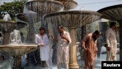 کراچی: گرمی سے ستائے افراد ایک سڑک پر بنے فوارے کے نیچے کھڑے ہیں۔ (فائل فوٹو)