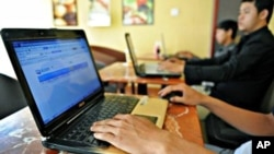 Cambodian men using the Internet at a coffee shop in Phnom Penh.