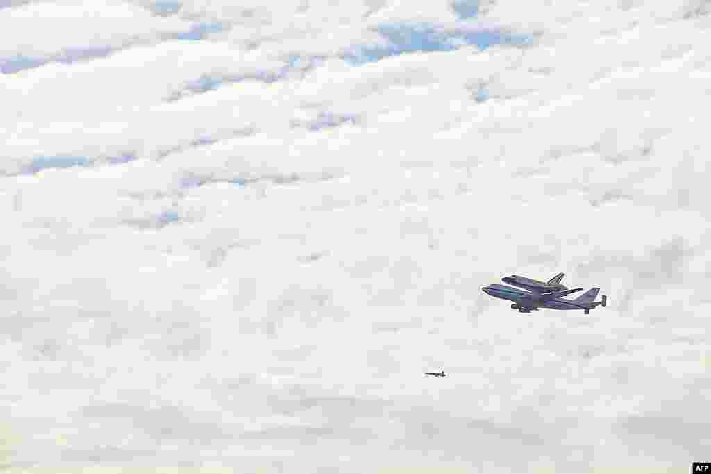 Space shuttle Discovery atop a 747 carrier jet flying over the National Mall in Washington, April 17, 2012. (VOA-A. Klein)