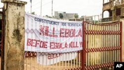 In this photo taken on Sunday, Sept. 14, 2014, a sign reading 'Kill Ebola Before Ebola Kill You', on a gate forming part of the country's Ebola awareness campaign in the city of Freetown, Sierra Leone. Shoppers crowded streets and markets in Sierra Leone's capital on Thursday, Sept. 18, stocking up for a three-day shutdown that authorities will hope will slow the spread of the Ebola outbreak that is accelerating across West Africa.