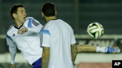 Argentina's Lionel Messi, left, kicks the ball next to teammate Ezequiel Lavezzi during an official training session at Vasco da Gama Stadium a day before the World Cup soccer final between Germany and Argentina in Rio de Janeiro, Brazil, July 12, 2014.
