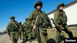 一批據說是俄羅斯的軍人在烏克蘭克里米亞的一個烏克蘭軍事設施前走過。