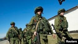 Војници, за кои се претпоставува дека припаѓаат на руските сили, минуваат низ село во близината на Симферопол.
