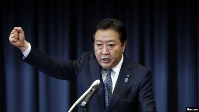 Japan's Prime Minister Yoshihiko Noda raises his fist as he makes a speech to his party's lawmakers at his party's meeting after the dissolution of the lower house in Tokyo, November 16, 2012.