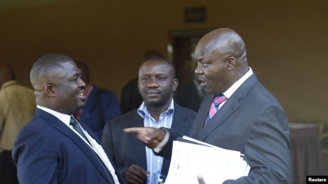 Roger Lumbala (R), a former member of parliament in the Democratic Republic of Congo who joined the M23 rebel group, chats with colleagues shortly after attending a peace talk meeting in Uganda's capital Kampala, January 11, 2013.