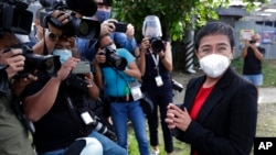 FILE - Rappler CEO Maria Ressa stands in front of reporters outside the Court of Tax Appeals in Manila, Philippines, March 4, 2021.