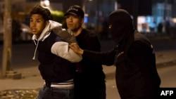 Сотрудники правоохранительных органов задерживают одного из протестующих. Тунис. 10 января 2018 г.