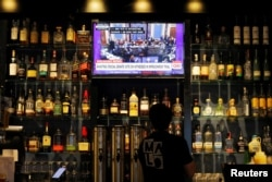 The U.S. Senate impeachment trial of President Donald Trump plays on a television at Malo restaurant in Des Moines, Iowa, Jan. 31, 2020.