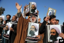 Iraqi Shiite protesters chant slogans against the Saudi government as they hold posters showing Sheikh Nimr al-Nimr, who was executed in Saudi Arabia last week, during a demonstration in Najaf, south of Baghdad, Iraq, Jan. 4, 2016.