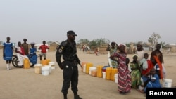 FILE - A Cameroonian police officer stands next to people waiting for water at the Minawao refugee camp for Nigerians who fled Boko Haram attacks in Minawao, Cameroon, March 15, 2016.