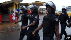 Police chant as they march through the streets of central Monrovia, Liberia, Oct. 11, 2011.