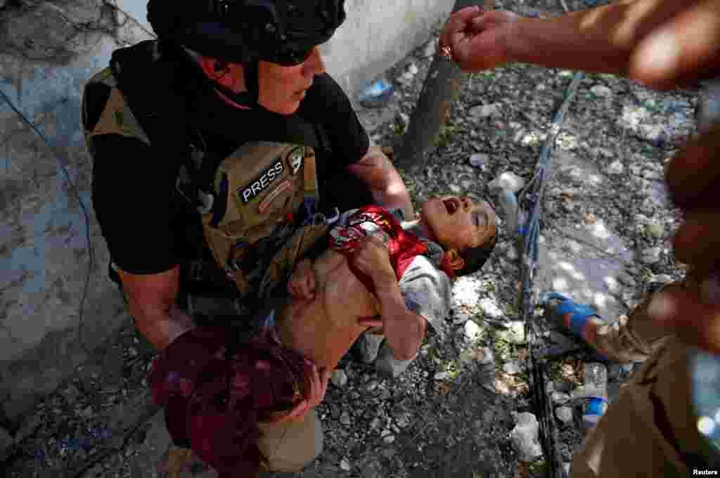 Musul'un batısında IŞİD ile savaşan Irak ordusundan bir asker susuz kalmış bir çocuğa su verirken