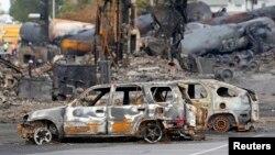 Mobil-mobil yang terbakar hangus terlihat di dekat lokasi ledakan tangki minyak di Lac Megantic, Quebec, Kanada (9/7).