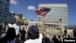 FILE - A woman waves a U.S flag in Havana, July 20, 2015.