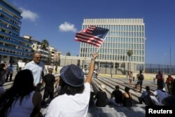 A woman waves a U.S flag in front of the U.S. Interests Section, in Havana, July 20, 2015.
