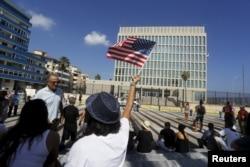 A woman waves a U.S flag in front of the U.S. Interests Section, in Havana, July 20, 2015.