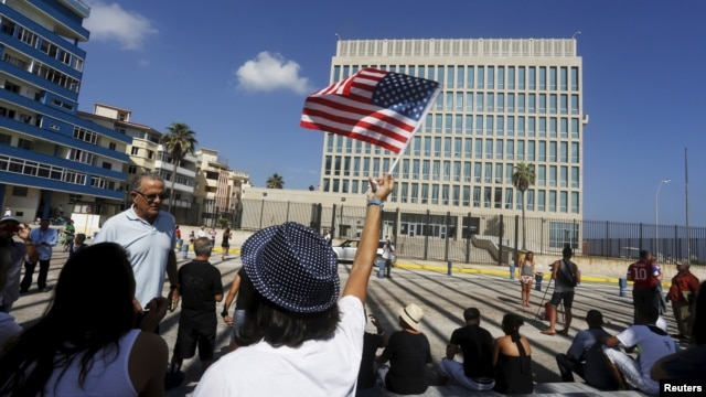 FILE - A woman waves a U.S flag in front of the U.S. Interests Section in Havana, July 20, 2015.