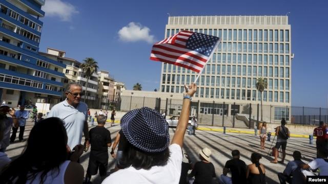 FILE - A woman waves a U.S flag in Havana, July 20, 2015.