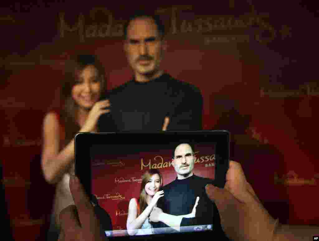 A Thai visitor poses with a newly launched wax figure of Steve Jobs, as her friend takes a picture at the Madame Tussauds wax museum in Bangkok, Thailand.