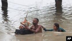 Dân làng lội qua nước lụt ở Rajanpur, Pakistan, hôm 23/7.