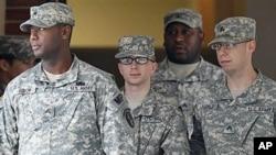 Army Private First Class Bradley Manning (C) is escorted out of a courthouse in Fort Meade, Maryland, December 21, 2011.
