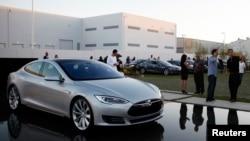 Tesla mengungkap sistem baru untuk mengganti baterai yang secara otomatis mengganti baterai yang mati dengan baterai yang sudah dicas penuh, Jumat (21/6).