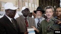 Eamon Omordha (kanan) Wakil Direktur urusan Referendum PBB menyerahkan surat suara referendum kepada Chan Reec Madut, ketua referendum Sudan Selatan (kiri), Kamis.
