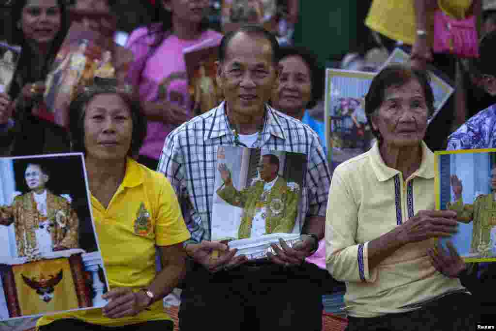 Well-wishers hold pictures of Thailand's King Bhumibol Adulyadej, Dec. 4, 2013,as they camp outside the palace where he is staying in Hua Hin, Prachuap Khiri Khan province, Thailand, a day before his birthday.