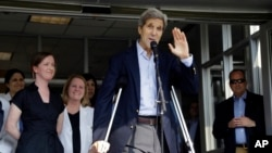 U.S. Secretary of State John Kerry waves after speaking to reporters as he is discharged from Massachusetts General Hospital in Boston, June 12, 2015.