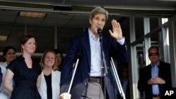 Menteri Luar Negeri AS John Kerry melambaikan tangan setelah berbicara kepada wartawan di Boston (12/6). (AP/Elise Amendola)