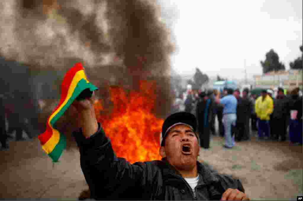 Dec. 29: Holding up a Bolivian flag in front of a bonfire, a demonstrator shouted slogans against increases in the price of fuel in El Alto. Bolivians were protesting a 73 percent jump in gasoline prices and and 83 percent rise in the price of diesel fuel